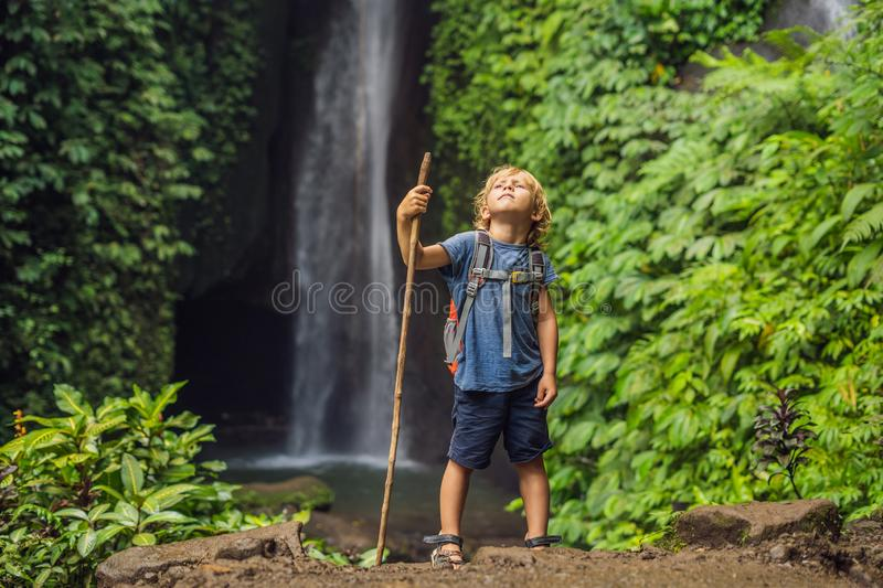 Boy with a trekking stick on the background of Leke Leke waterfall in Bali island Indonesia. Traveling with children. Concept stock photo