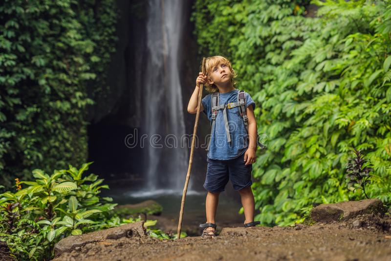 Boy with a trekking stick on the background of Leke Leke waterfall in Bali island Indonesia. Traveling with children. Concept stock photography