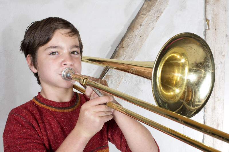 Boy with a trombone royalty free stock photos