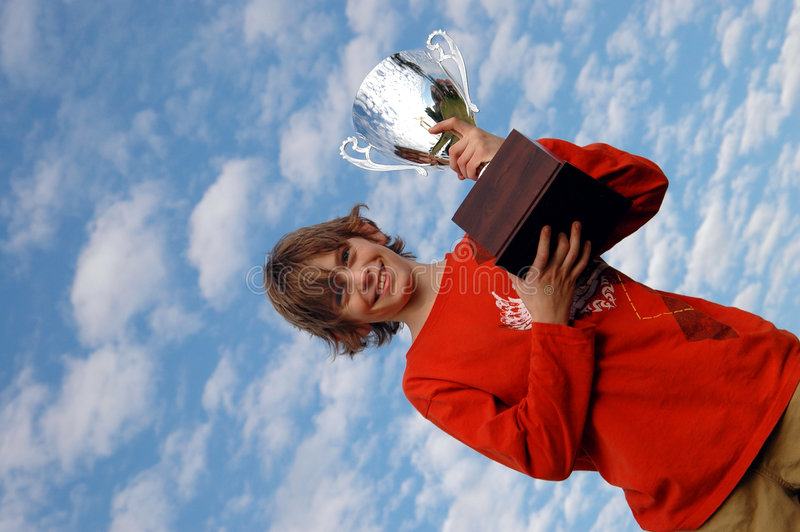 Boy with trophy. A happy boy holding up a big trophy (sky background