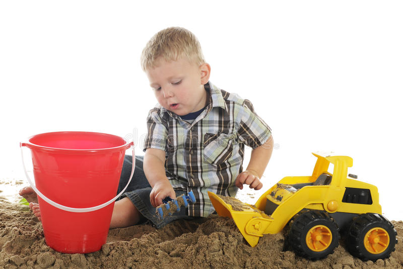 Boy, Truck, Sand and Pail. A young preschooler using his truck and hand rake to scoop up sand for his pail. On a white background royalty free stock images