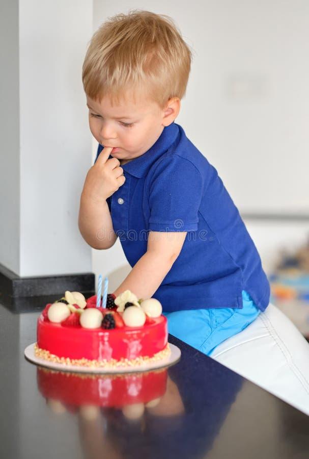 Boy trying birthday cake royalty free stock image