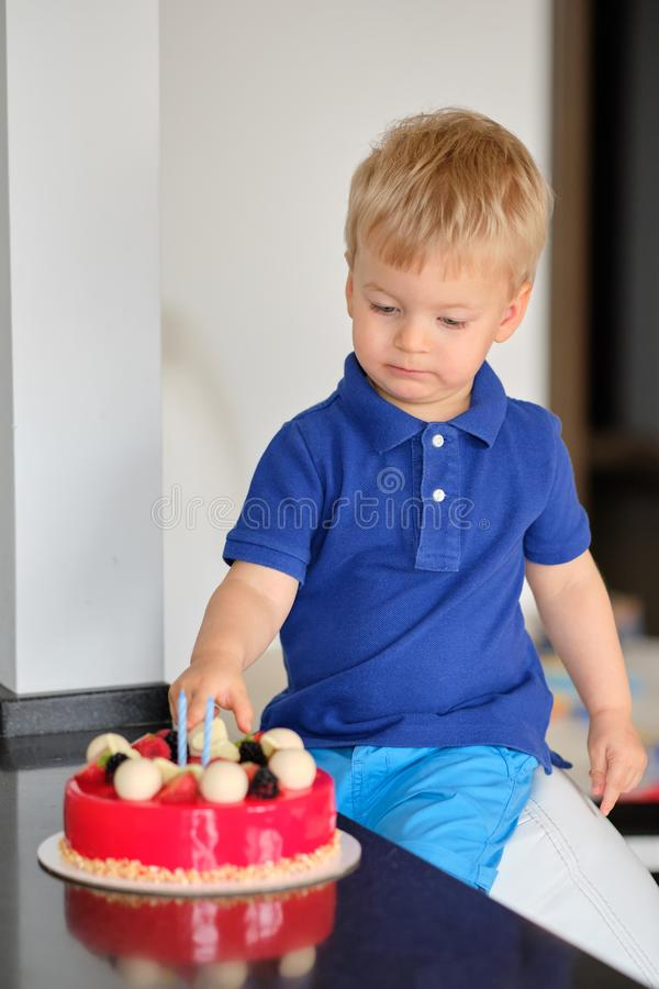 Boy trying birthday cake royalty free stock images