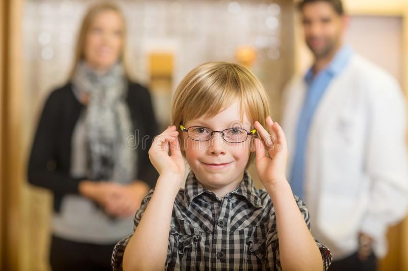 Boy Trying Glasses With Optometrist And Mother At. Portrait of smiling boy trying glasses with optometrist and mother standing in background at store royalty free stock image