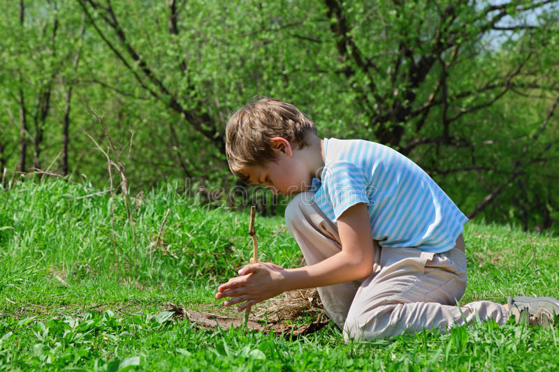Download Boy Trying To Take Flame By Primitive Way By Stick Stock Photo - Image of primeval, people: 17889048