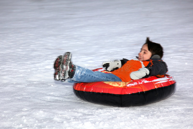 Boy Tubing Down Snowy Hill. royalty free stock image