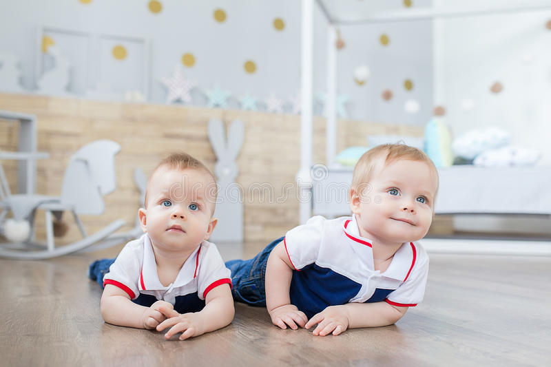 Boy twins playing on the floor stock photos