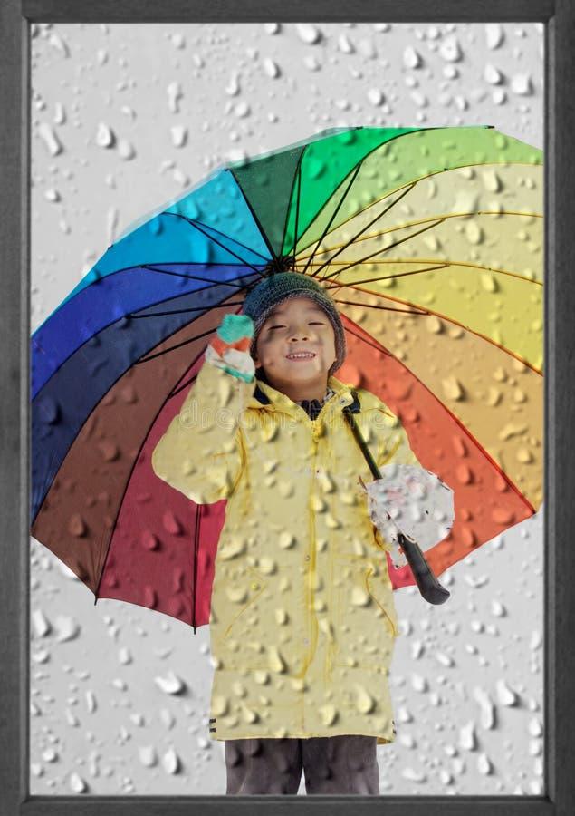 Boy with umbrella in winter rain stock photo