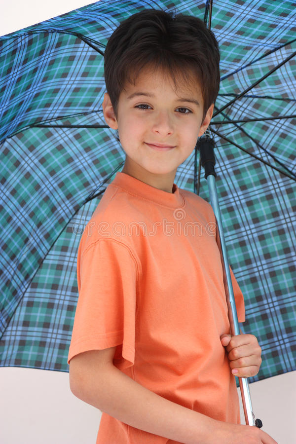 A boy under an open umbrella stock images