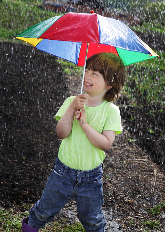 Boy under an umbrella stock image