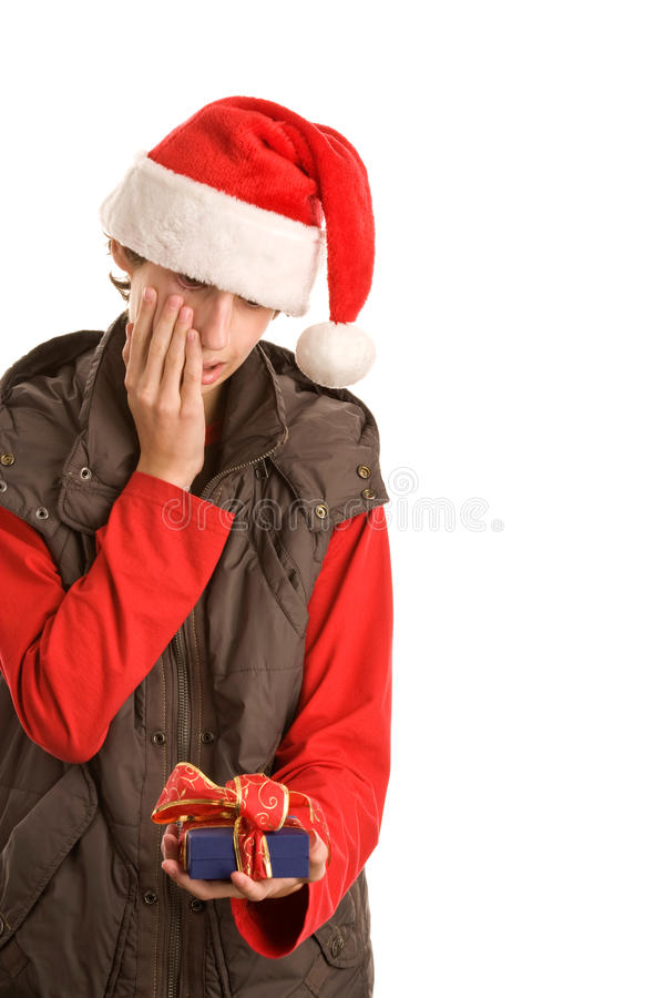 Boy with unwanted gift. Portrait of young worried christmas boy holding unwanted gift isolated on white background. What is it royalty free stock images