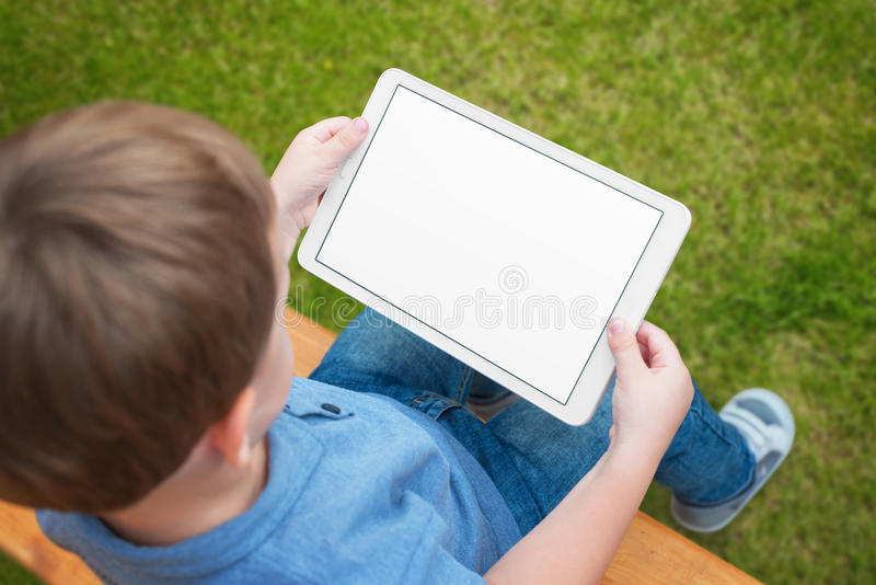 Boy use tablet with isolated white screen for mockup. Child playing game, surfing or watching cartoon stock photos