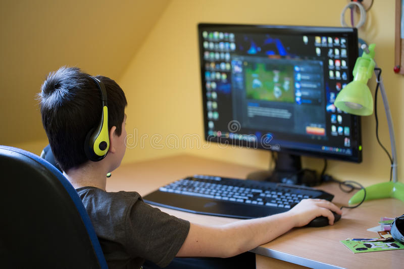 Boy using computer at home, playing game. Teenager using computer at home with headphones, play game in his child room