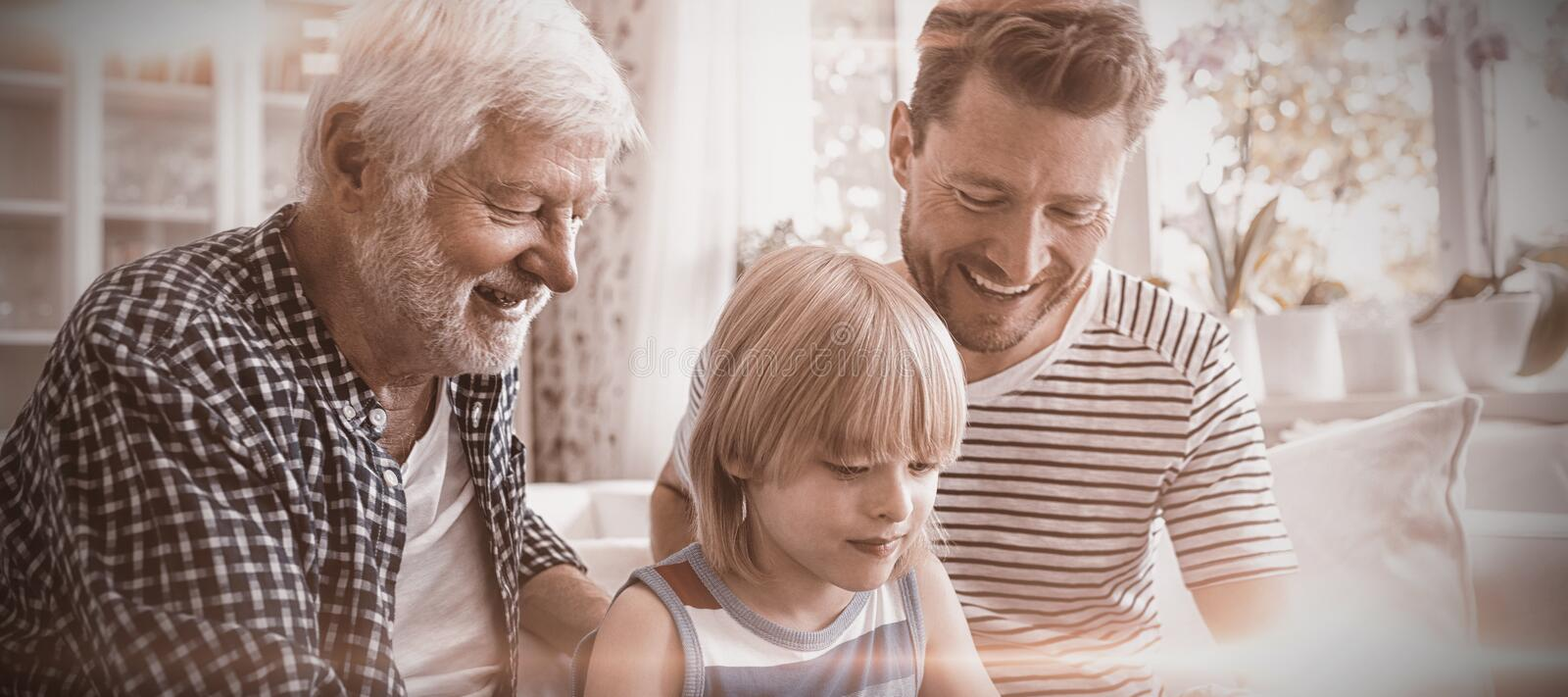Boy using digital tablet with his father and grandfather in living room stock photography