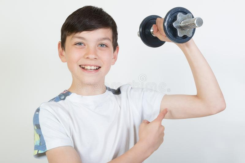 Boy using dumbbell weights. Boy exercising using dumbbell weights stock photography