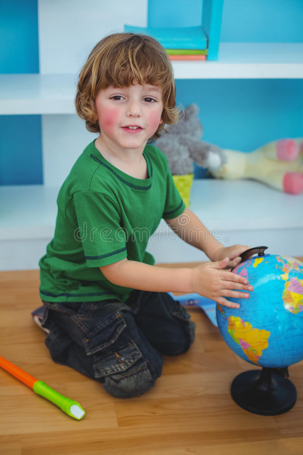 Boy using a globe of the world. At the desk royalty free stock images