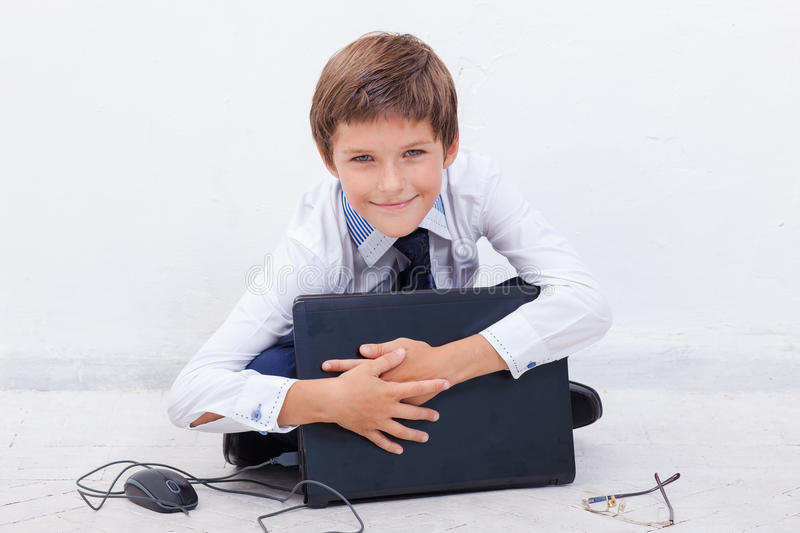 Boy using his laptop computer. The smiling boy using his laptop computer on white background stock photography