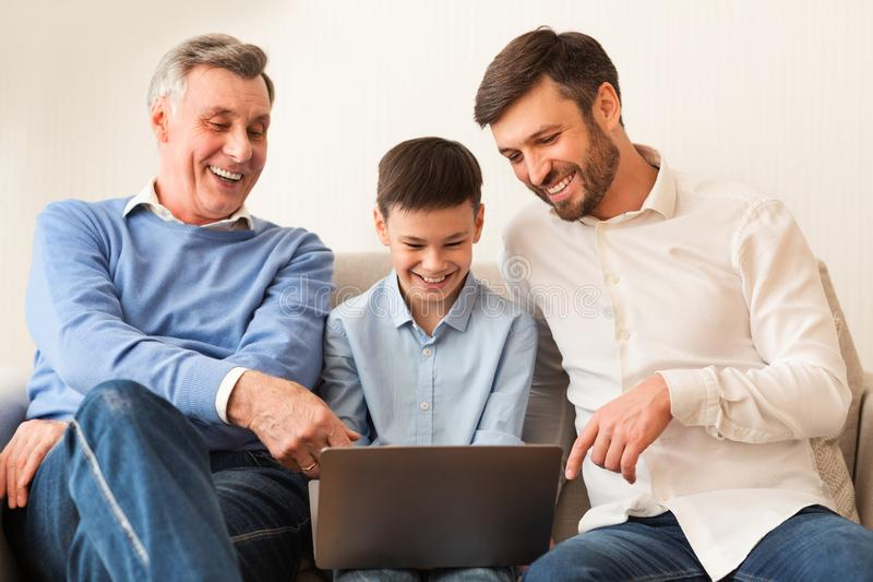 Boy Using Laptop Sitting Between Dad And Grandfather Sitting Indoor stock photo