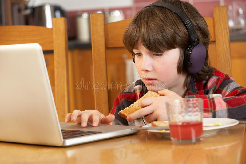 Boy Using Laptop Whilst Eating Breakfast. In Kitchen stock photo
