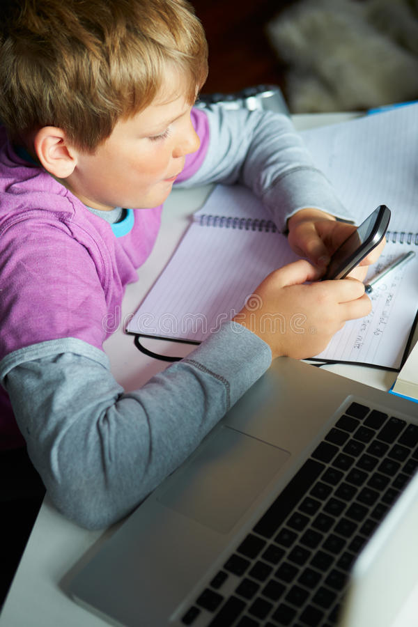 Boy Using Mobile Phone Instead Of Studying In Bedroom Royalty Free Stock Photo