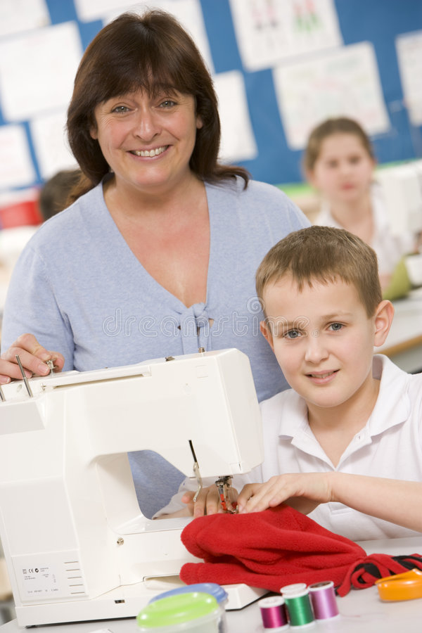 Boy using a sewing machine royalty free stock photography