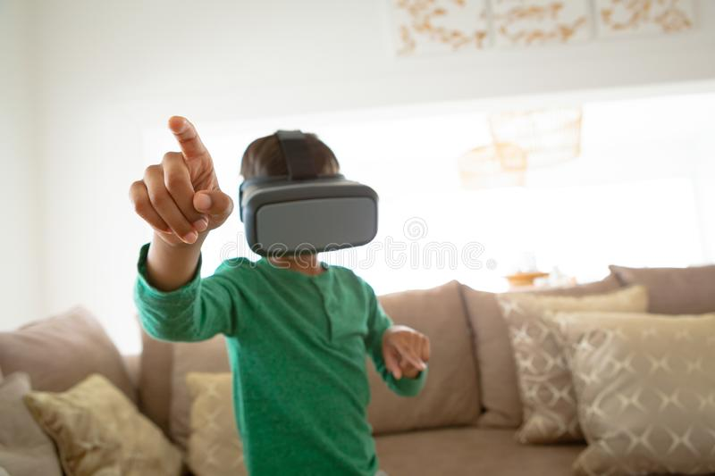 Boy using virtual reality headset in living room at comfortable home royalty free stock image