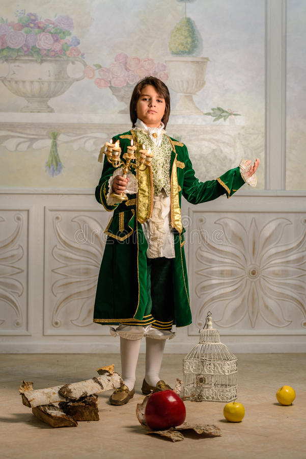 Boy in vintage clothes. Boy stands in vintage clothes with candlestick in hands royalty free stock image