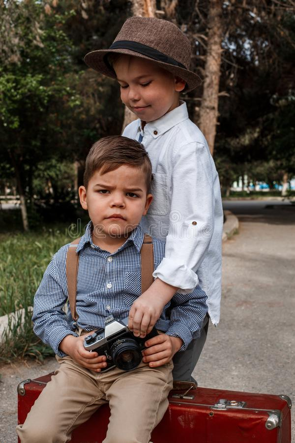A boy in vintage clothes takes pictures of another boy sitting on a vintage suitcase with a vintage camera.  royalty free stock photography