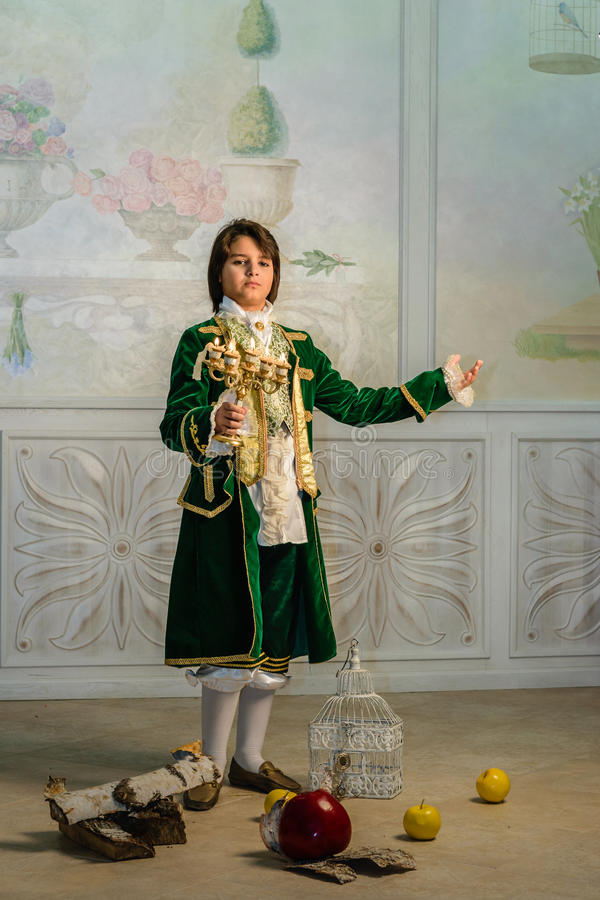 Boy in vintage costume. Boy stands in vintage clothes with candlestick in hands royalty free stock photos