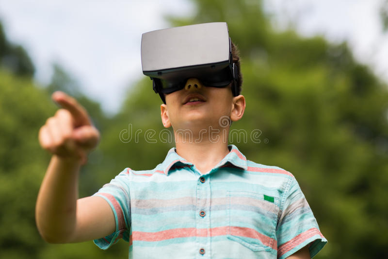 Boy with virtual reality headset outdoors. Childhood, augmented reality, technology and people concept - boy with virtual headset or 3d glasses playing game stock photos