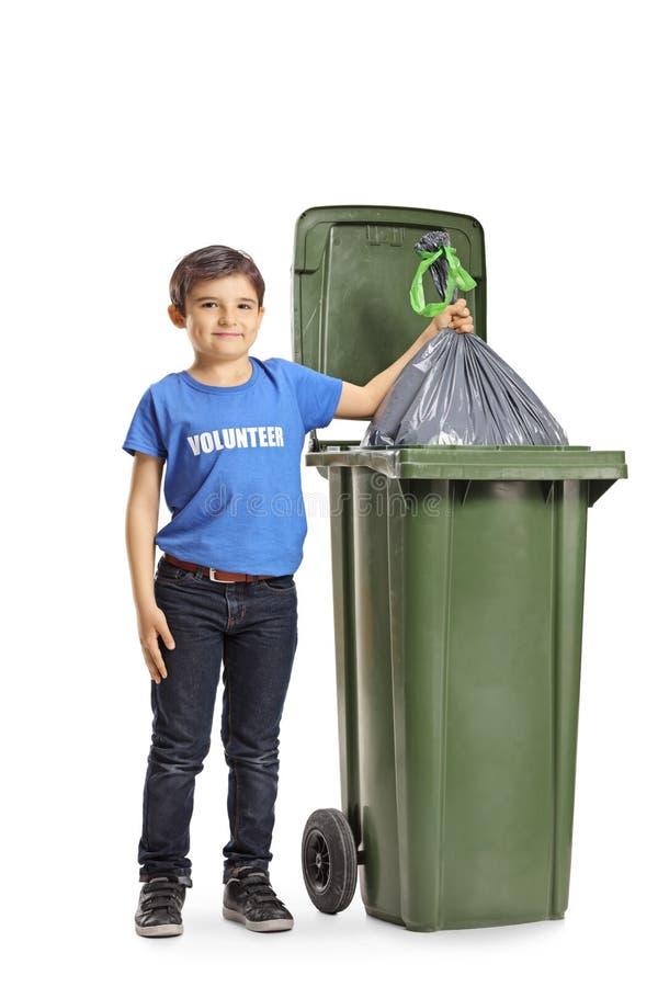 Boy volunteer throwing a waste bag into a bin. Full length portrait of a boy volunteer throwing a waste bag into a bin isolated on white background stock image