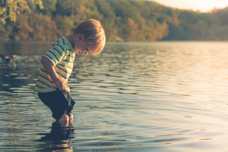 Boy Wading into Lake stock photos
