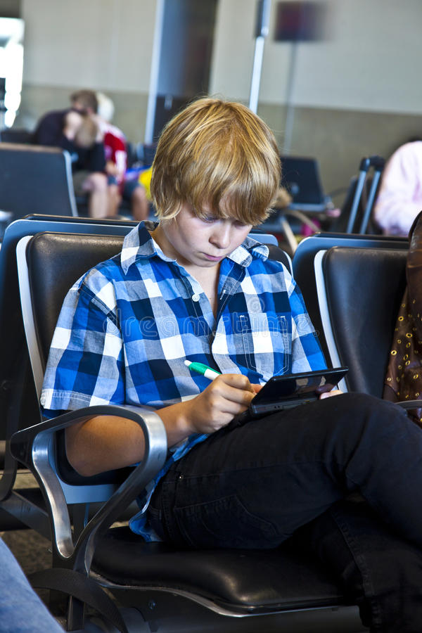 Boy is waiting for departure at the airport royalty free stock photography