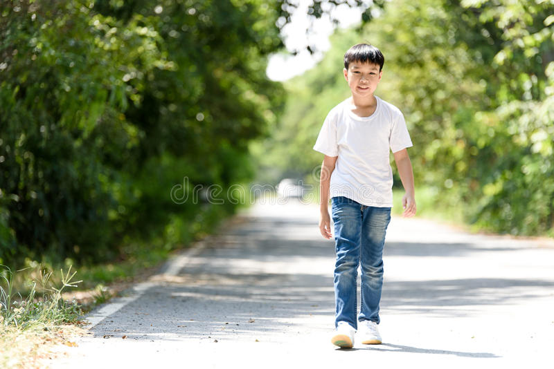 Boy walk on the road. Young Thai boy in blue jean walk on the road in the park royalty free stock photos