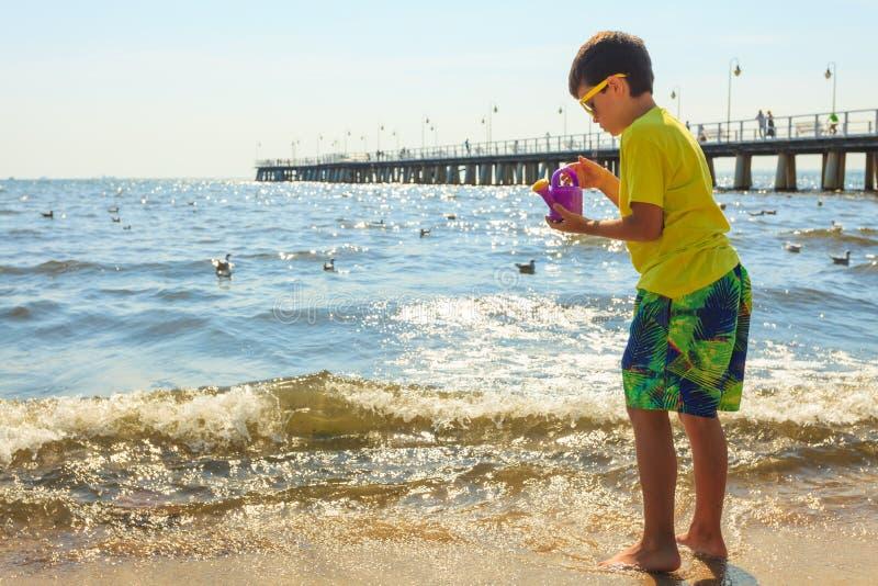 Boy walking on beach. stock photos