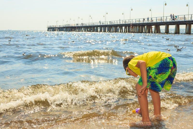Boy walking on beach. stock photo