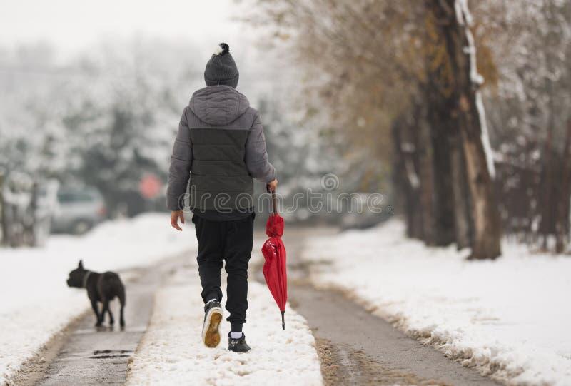 Boy walking down the snowy street stock photos