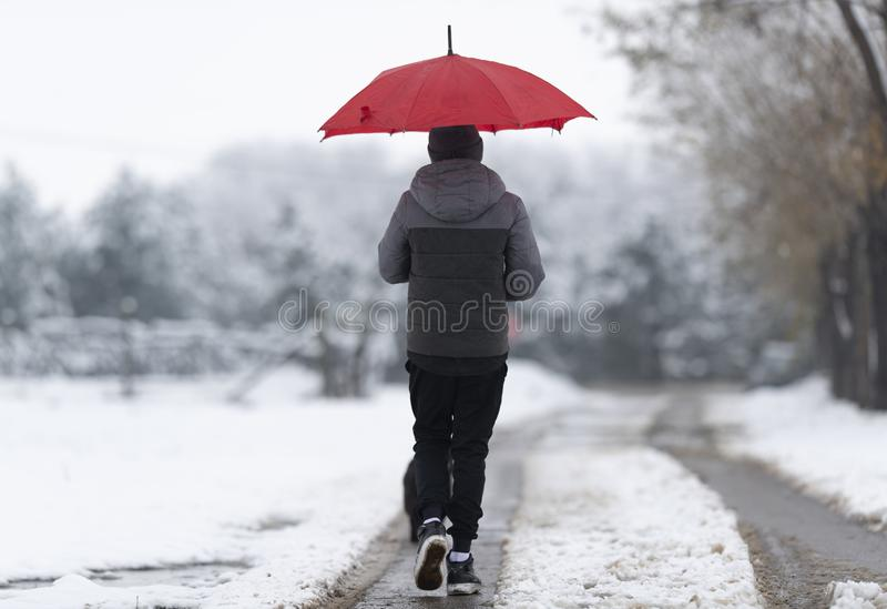 Boy walking down the snowy street stock photo