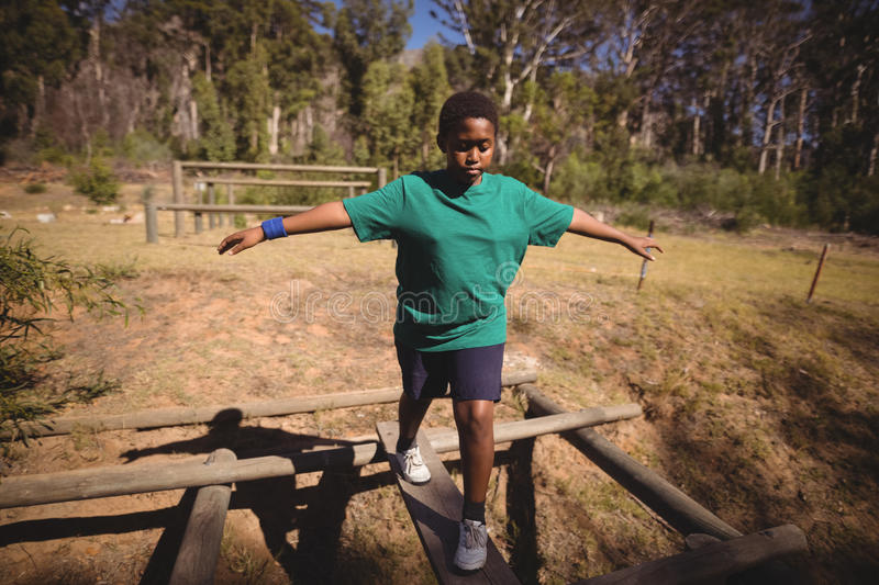 Boy walking on obstacle during obstacle course royalty free stock photo