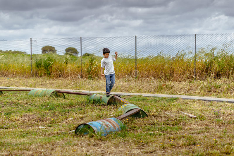 Boy walking over barrels in playground area at Spanish Aerodrome. royalty free stock images