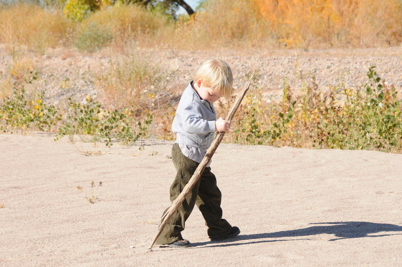 Download Boy Walking On Sand With Stick Stock Photo - Image: 12225536