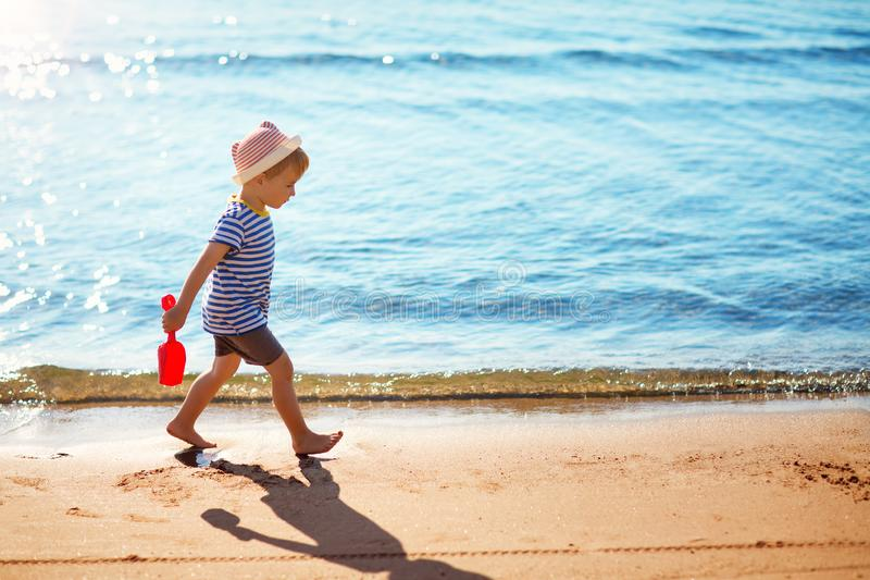 Boy walking at sea in straw hat royalty free stock photos