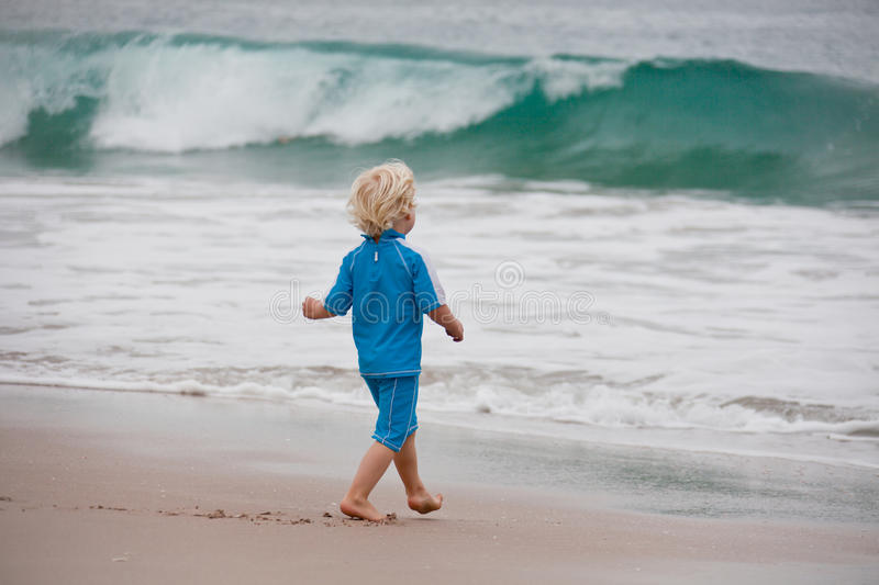 Download Boy walking towards waves stock image. Image of small - 17507735