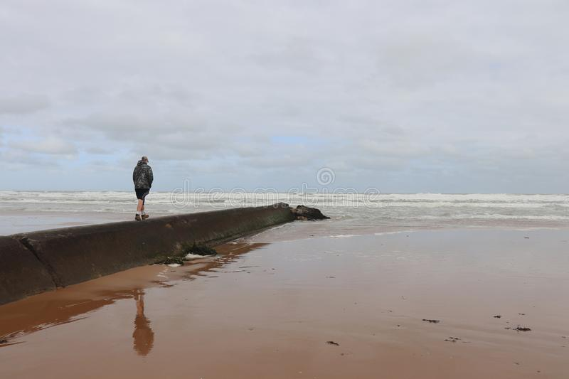 Boy walks out to the ocean at Omaha Beach stock photography
