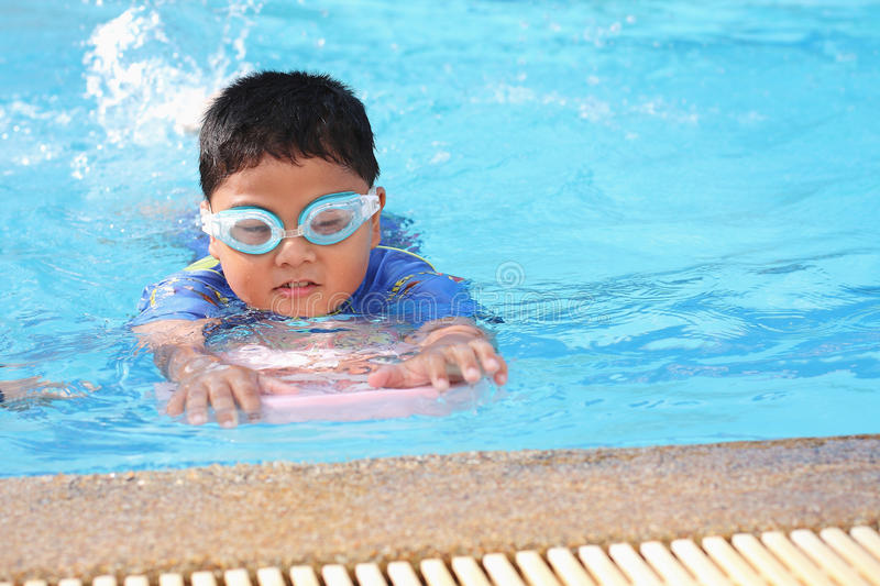 The boy was swimming in the pool. The boys were playing in the swimming pool royalty free stock photography