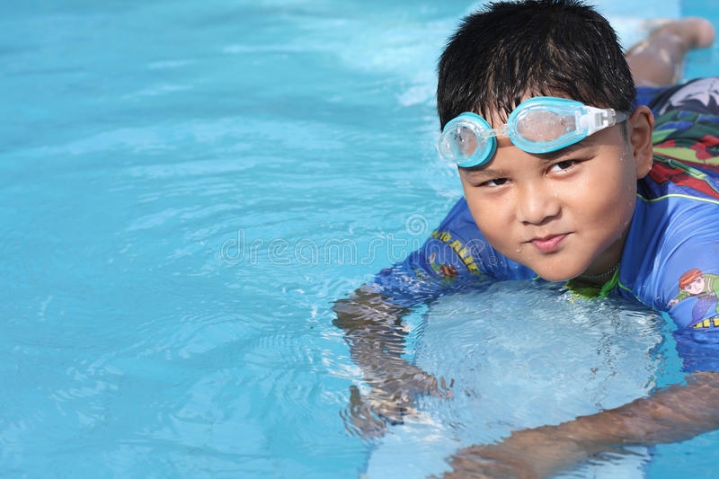 The boy was swimming in the pool. The boys were playing in the swimming pool royalty free stock photos