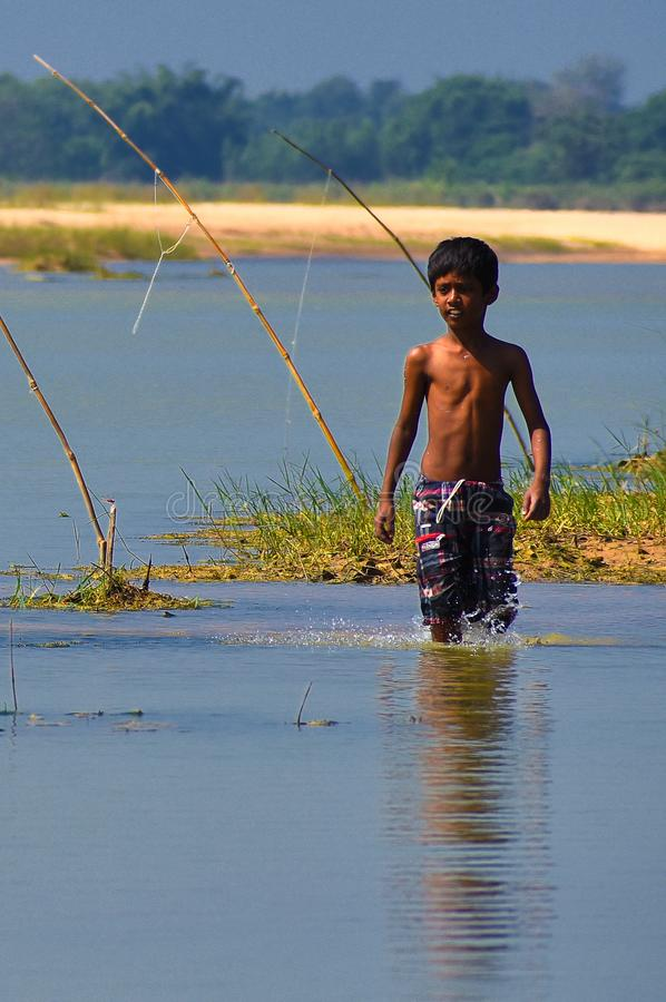A boy was walking in the low water of a river after casting his fishing rods stock photography