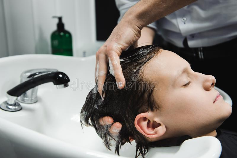 A boy is washed by the hairdresser in the barbershop. A boy is washed by the hairdresser in the barbershop stock photo