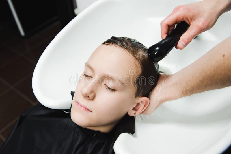 A boy is washed by the hairdresser in the barbershop. A boy is washed by the hairdresser in the barbershop stock image