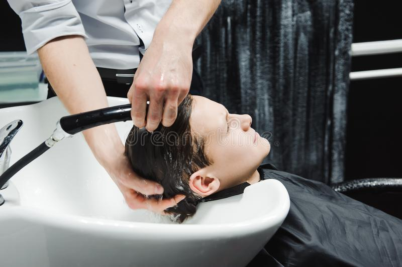 A boy is washed by the hairdresser in the barbershop.  royalty free stock photo